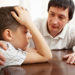 father comforts a sad bullied child.
