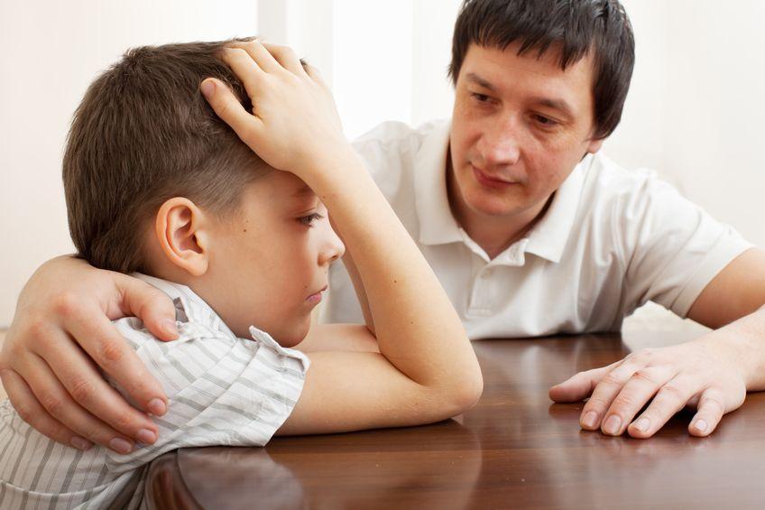 father comforts a sad bullied child.